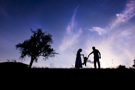 Silhouettes of happy parents having fun with their children photo