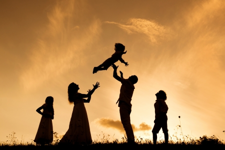parents love: Silhouettes of happy parents having fun with their children