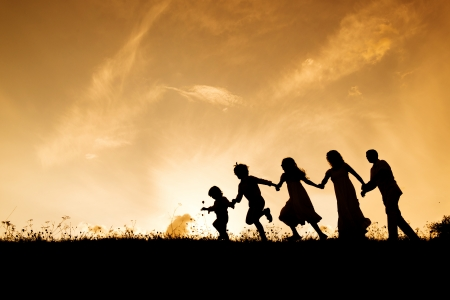 children playing together: Silhouettes of happy parents having fun with their children