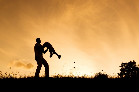 Silhouette of happy father having fun with his son photo