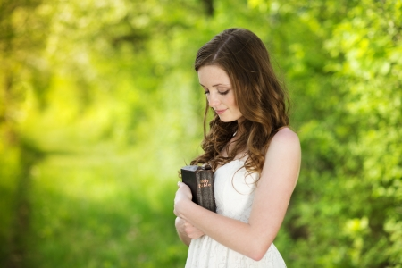日当たりの良い自然の中で聖書を持つ美しい女性です。
