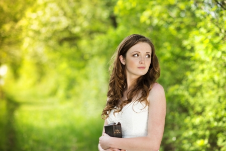 Beautiful woman with book is in sunny nature