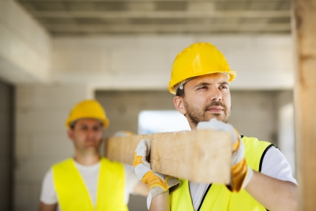 site: Construction workers collaborating on new house building Stock Photo