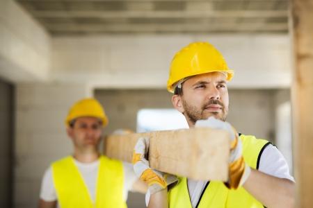 obreros trabajando: Trabajadores de la construcci�n colaborando en la construcci�n de viviendas nuevas
