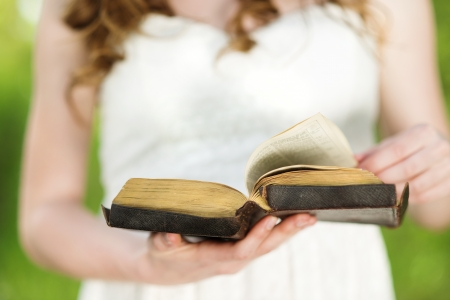 humbled: Beautiful woman with Bible is in sunny nature