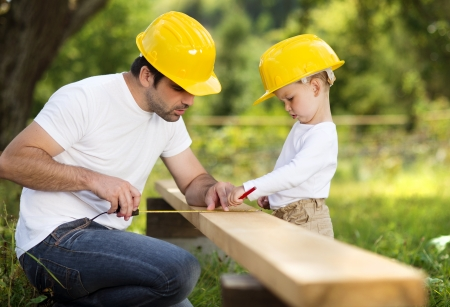 communication tools: Little son helping his father with building work Stock Photo