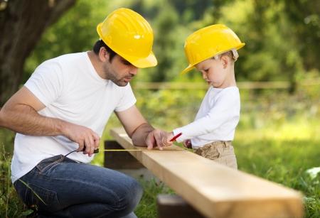 Little zoon helpt zijn vader met bouwwerkzaamheden Stockfoto