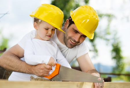 Little son helping his father with building work photo