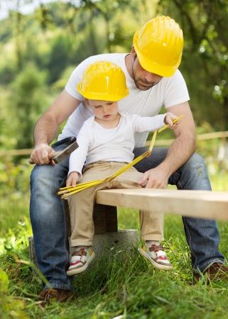 Zoontje helpen van zijn vader met bouwwerkzaamheden