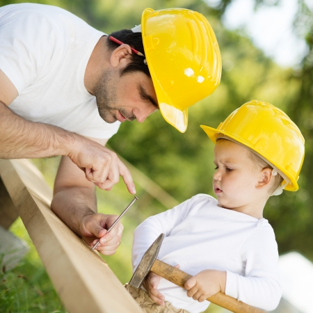 Little son helping his father with building work Stock Photo
