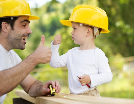 Little son helping his father with building work Stok Fotoğraf