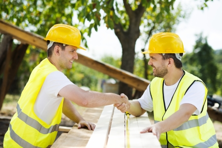 collaborating: Construction workers collaborating on new house building Stock Photo