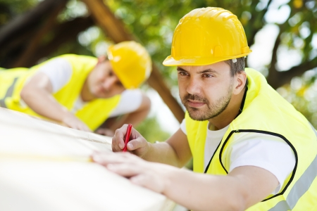 Construction workers collaborating on new house building Stok Fotoğraf