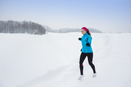 Athlete woman is running during winter in cold snow weather  photo