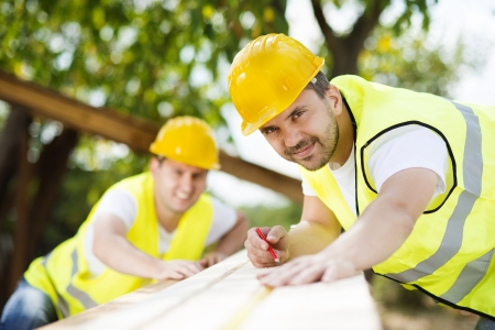 Construction workers collaborating on new house building Stock Photo