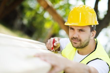 obreros trabajando: Trabajador de la construcci�n est� trabajando con vigas de madera Foto de archivo