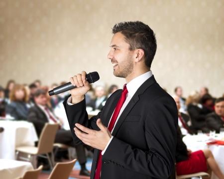 hablante: El hombre est? hablando en conferencia de negocios en interiores para los administradores Foto de archivo