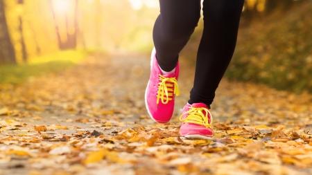 course � pied: Gros plan sur pieds d'un coureur courir dans les feuilles d'automne exercice d'entra�nement