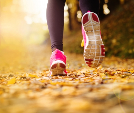 woman sport: Close up of feet of a runner running in autumn leaves training exercise