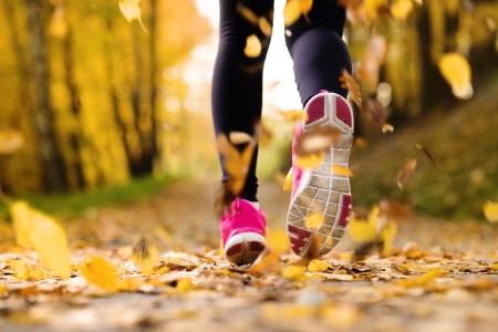cerrar: Primer plano de los pies de un corredor que se ejecuta en las hojas de otoño ejercicio de entrenamiento