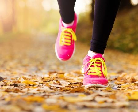 Närbild på fötter en löpare som körs i höstlöv övning