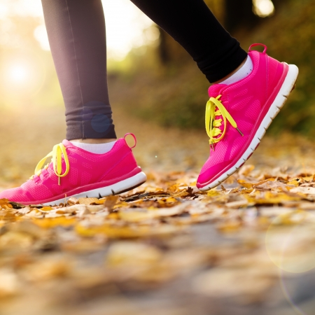 Close up of feet of a runner running in autumn leaves training exercise photo