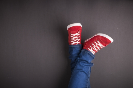 red shoes: Feet concept with red shoes on black background with space for text or symbol