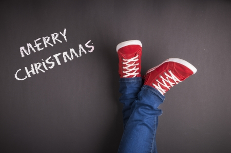 christmas concept: Christmas concept with red shoes and white chalk Stock Photo
