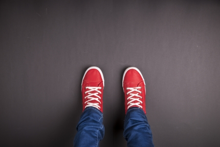 Feet concept with red shoes on black background with space for text or symbol