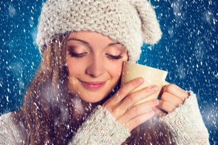 sue�os: Mujer hermosa en su�ter caliente con copos de nieve a su alrededor, sobre fondo azul Foto de archivo