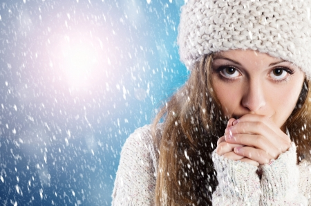 Beautiful woman in warm sweater with snowflakes around her, on blue background photo