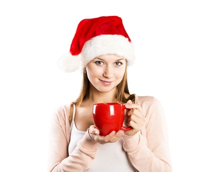 Beautiful woman with christmas hat is posing in studio  Isolated on white background  photo