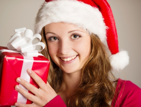 Beautiful smiling woman opening her christmas gift photo