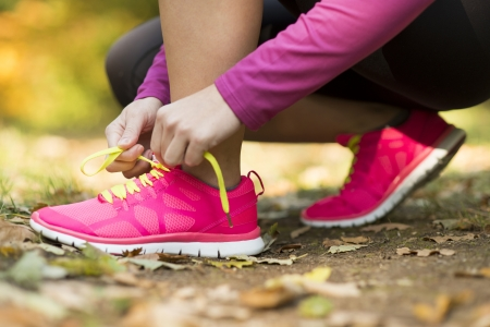 shoe: Close up of feet of a runner running in autumn leaves training exercise
