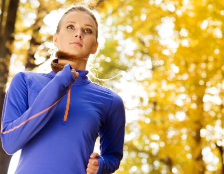 Bautiful running woman jogging in autumn nature photo