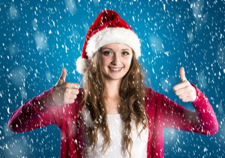Beautiful woman with christmas hat on blue winter background with snowflakes photo