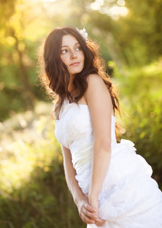 Portrait of beautiful bride in white wedding dress at the meadow photo