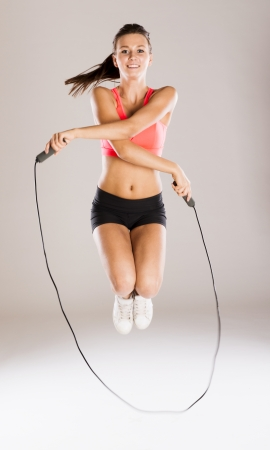 woman rope: Young active woman with rope is training in studio