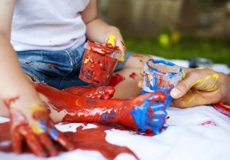 Cute child painting with vibrant colors in the garden photo
