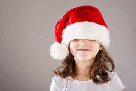 Happy small girl in large santa hat photo