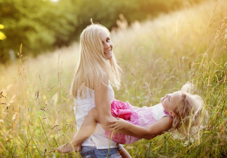 Happy young mother playing with her daughter photo