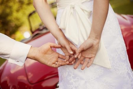 ゴージャスな花嫁と新郎の自然の中でレトロな車が赤を楽しんで