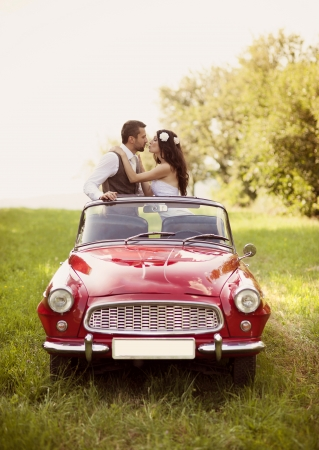 groom: Gorgeous bride and groom having fun with red retro car in nature Stock Photo