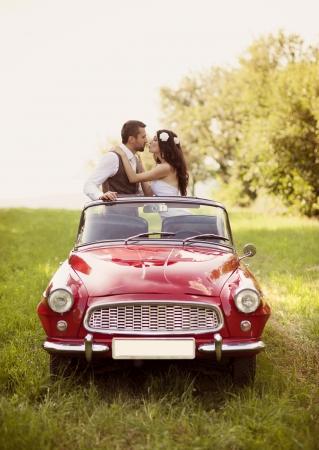 Prachtige bruid en bruidegom plezier met rode retro auto in de natuur Stockfoto