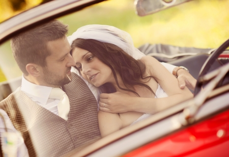 Gorgeous bride and groom having fun with red retro car in nature photo