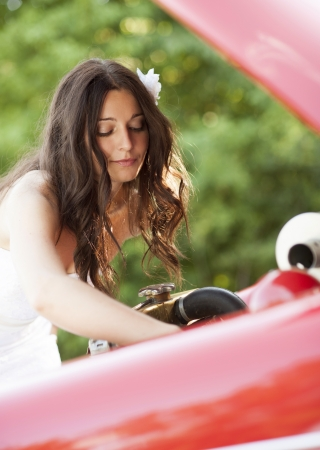 Beautiful brunette bride on a green meadow with retro car photo