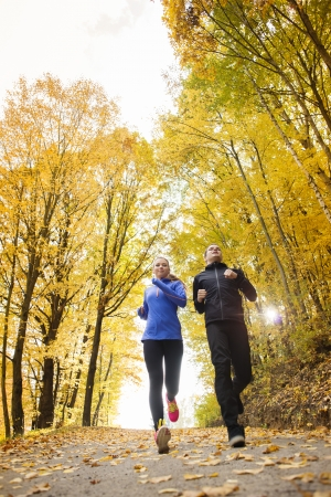 run out: Young running couple jogging in autumn nature