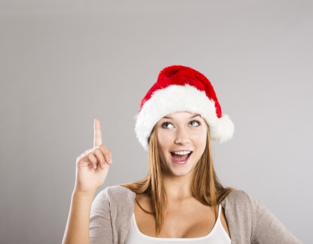forefinger: Portrait of attractive woman isolated on gray, studio shot in christmas hat