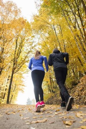 Young running couple jogging in autumn nature