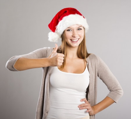 woman sweater: Portrait of attractive woman isolated on gray, studio shot in christmas hat